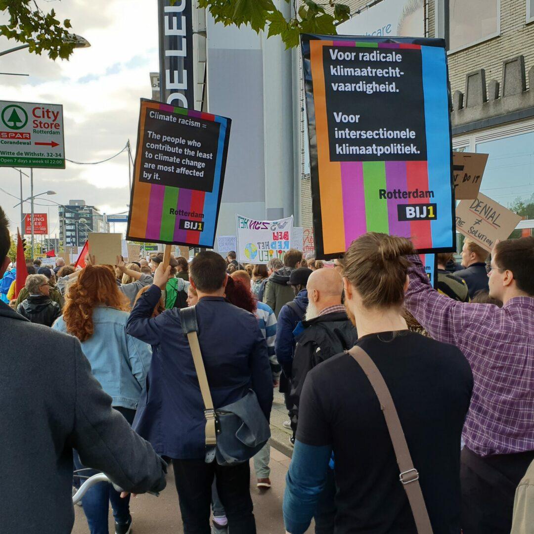 """Een groep mensen loopt door een stad met protestborden waar de BIJ1 kleuren en logo op te zien zijn. Er staat op: """"Voor radicale klimaatrechtvaardigheid. Voor intersectionele klimaatpolitiek. Rotterdam BIJ1."""" Op een ander bord: """"Climate racism = The people who contribure the least to climate change are most affected by it. Rotterdam BIJ1"""""""