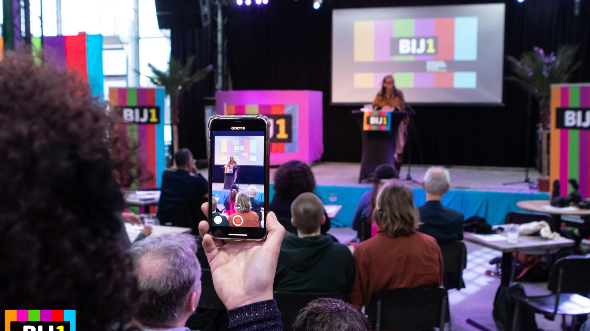 Een foto van het BIJ1 podium tijdens de kick off op 2 februari 2020. Veel BIJ1 logo's. Professor Gloria Wekker staat op het podium te spreken. Iemand filmt haar met een mobiele telefoon.