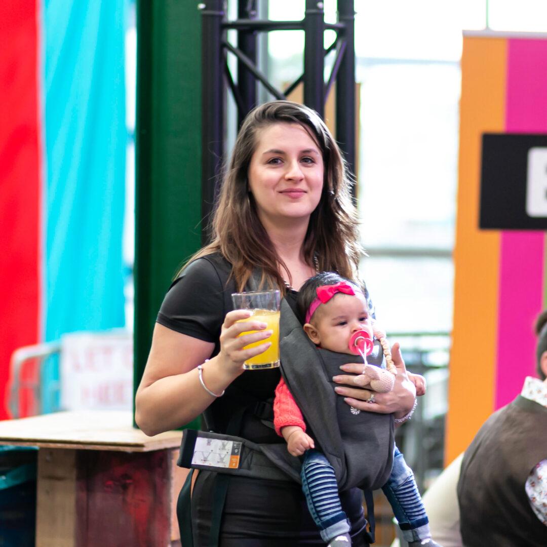 Een vrouw met witte huidskleur en bruin haar kijkt vrolijk in de camera. Ze houdt een glas sinaasappelsap vast in haar ene hand en draagt een baby in een draagzak op haar buik. Op de achtergrond grote kleurrijke BIJ1 banners en nog een oudere witte man met grijs haar.