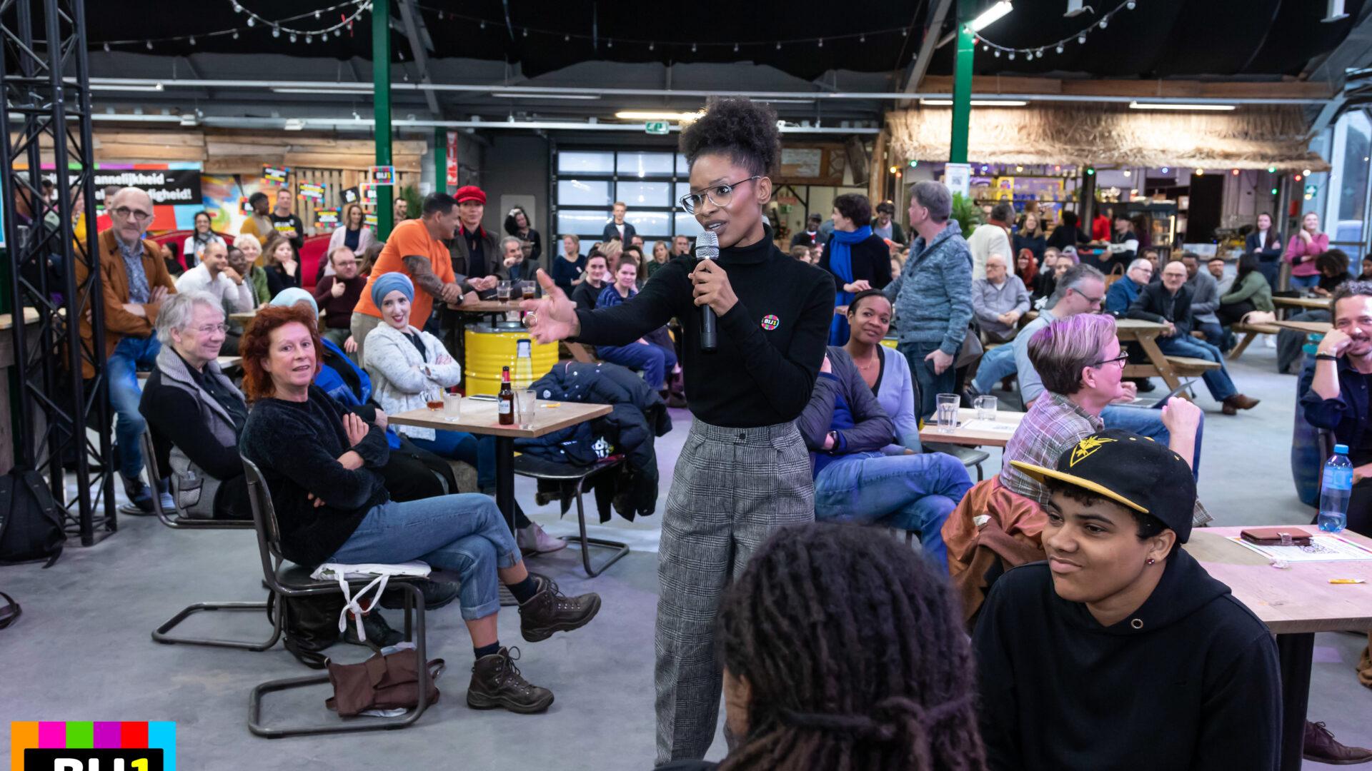 Sylvana Simons, zwarte vrouw met haar krullende haar opgestoken, spreekt in een microfoon die ze vasthoudt, terwjl ze haar andere hand uitnodigend uitsteekt. Ze staat temidden van een ruimte waar veel mensen zitten aan tafeltjes. Het ziet er feestelijk uit.