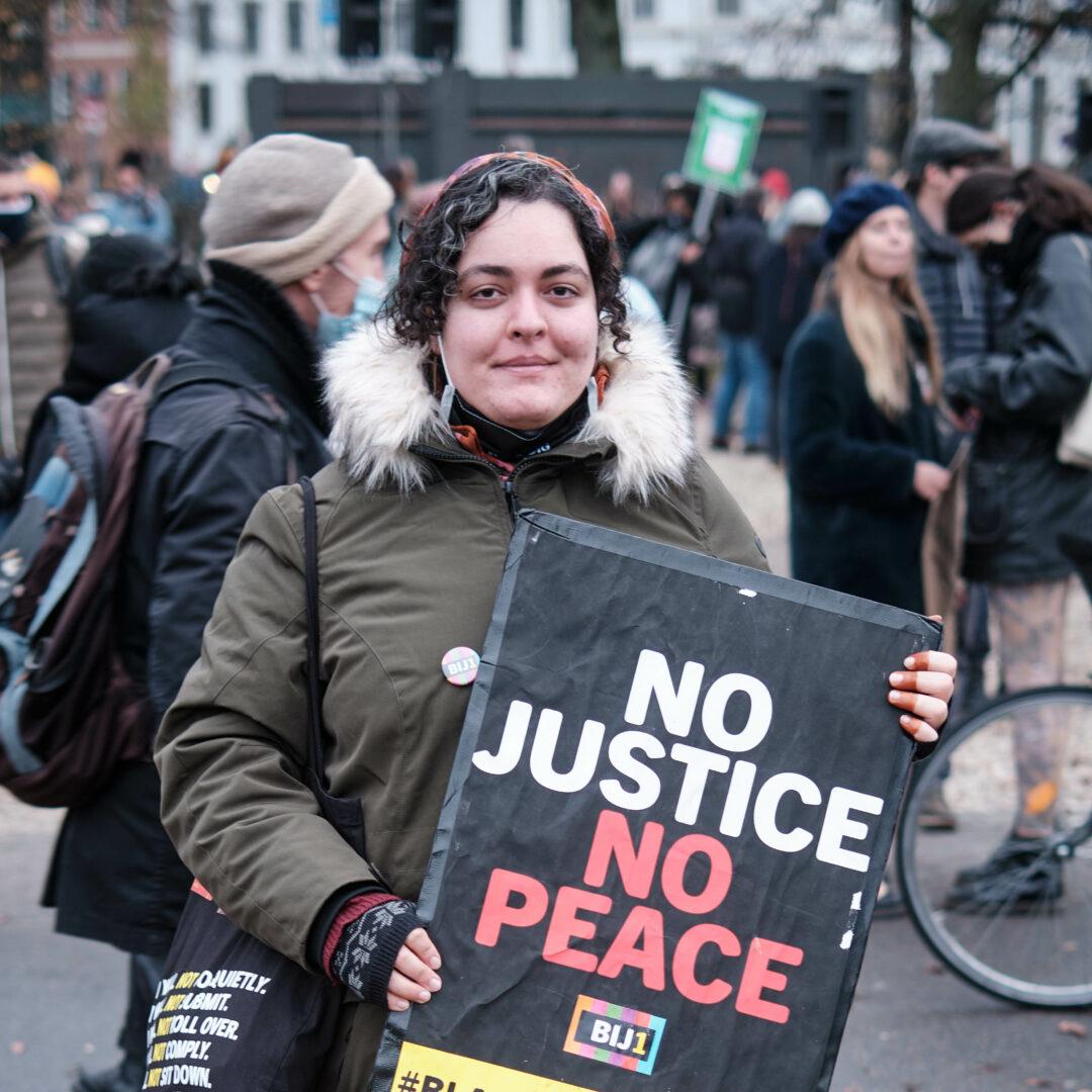 """Een lichtbruine vrouw met krullen kijkt de camera in en houdt een bord vast waarop staat """"No Justice No Peace"""" en het BIJ1 logo. Op de achtergrond zijn meer mensen te zien."""