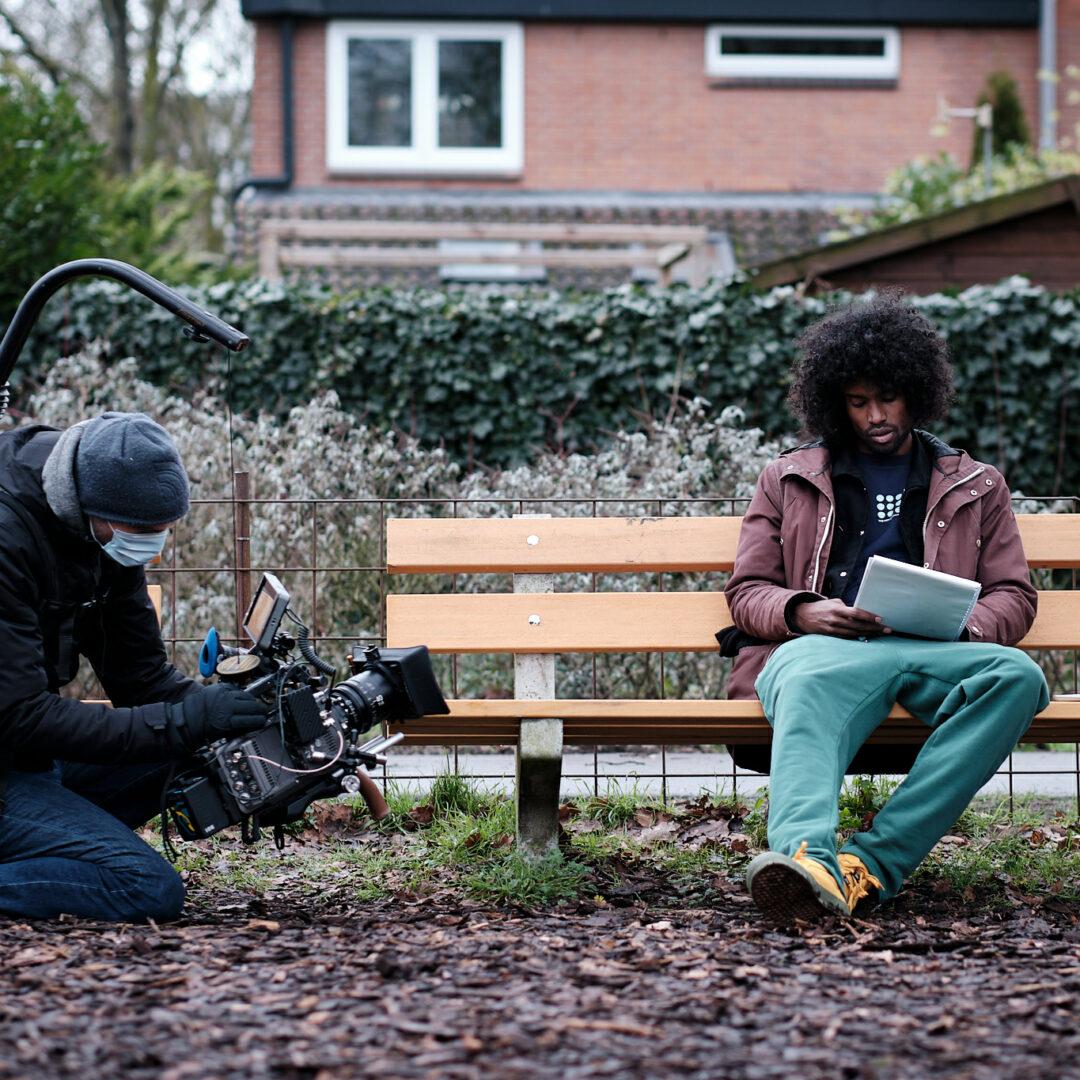 Daryll Ricardo Landbrug zit op een bankje in een parkje in een woonwijk. Hij leest een stapel papieren in zijn hand. Linksvoor knielt een man met mondkapje en een muts op die hem met een grote camera en apparatuur aan het filmen is.