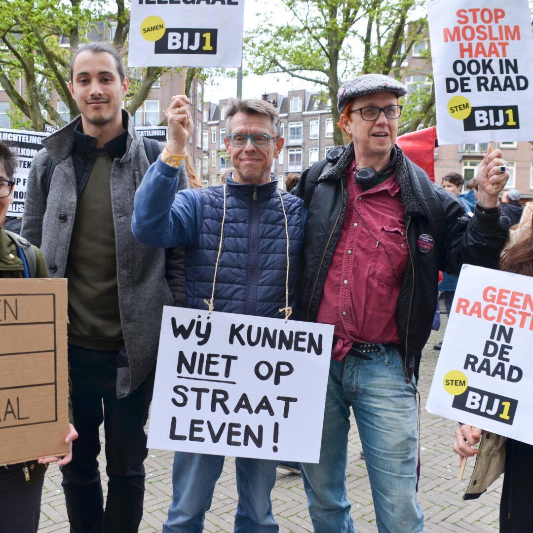 """Vijf mensen op een rij die vrolijk rondkijken, sommigen kijken in de camera. Ze houden bordjes vast met """"Geen mens is illegaal"""", """"Wij kunnen niet op straat leven!"""", """"Stop Moslimhaat ook in de raad, stem BIJ1"""", """"Geen racisten in de raad - stem BIJ1"""" en """"Queer Support Refugees. How about you?"""""""