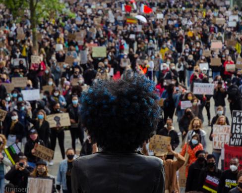Een persoon met een afro-kapsel spreekt de menigte toe bij een BLM-protest