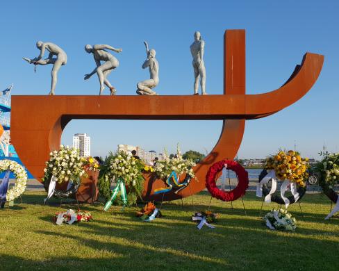 Het nationaal slavernijmonument, een metershoge roestbruine balk met gebogen vorm eronder, met daarop vier menselijke figuren in diverse houdingen. Er staan grote bloemenkransen voor het monument.