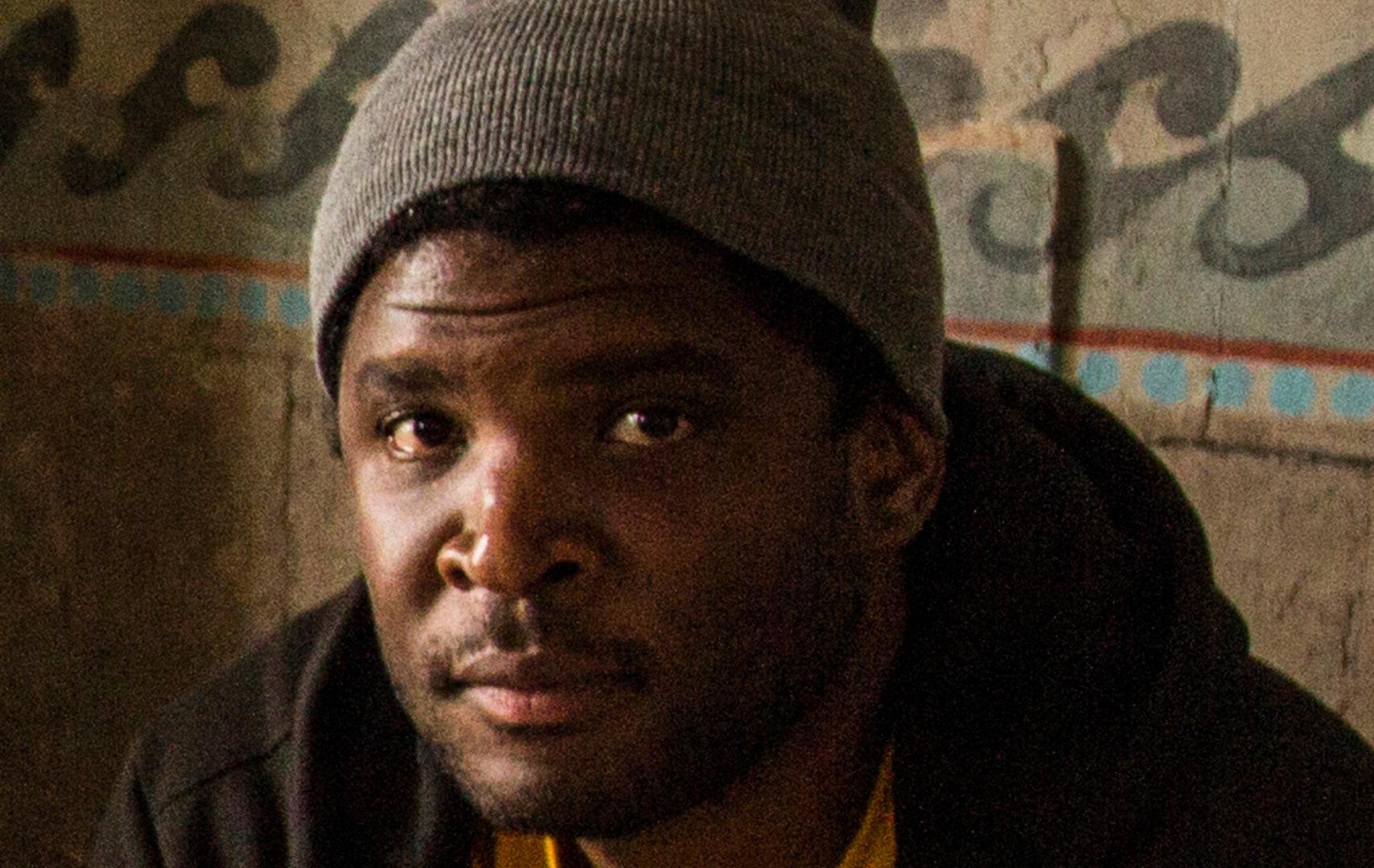 Portretfoto van Quinsy Gario. Hij is een zwarte man. Hij draagt een grijze muts, een geel shirt en een zwart vest.