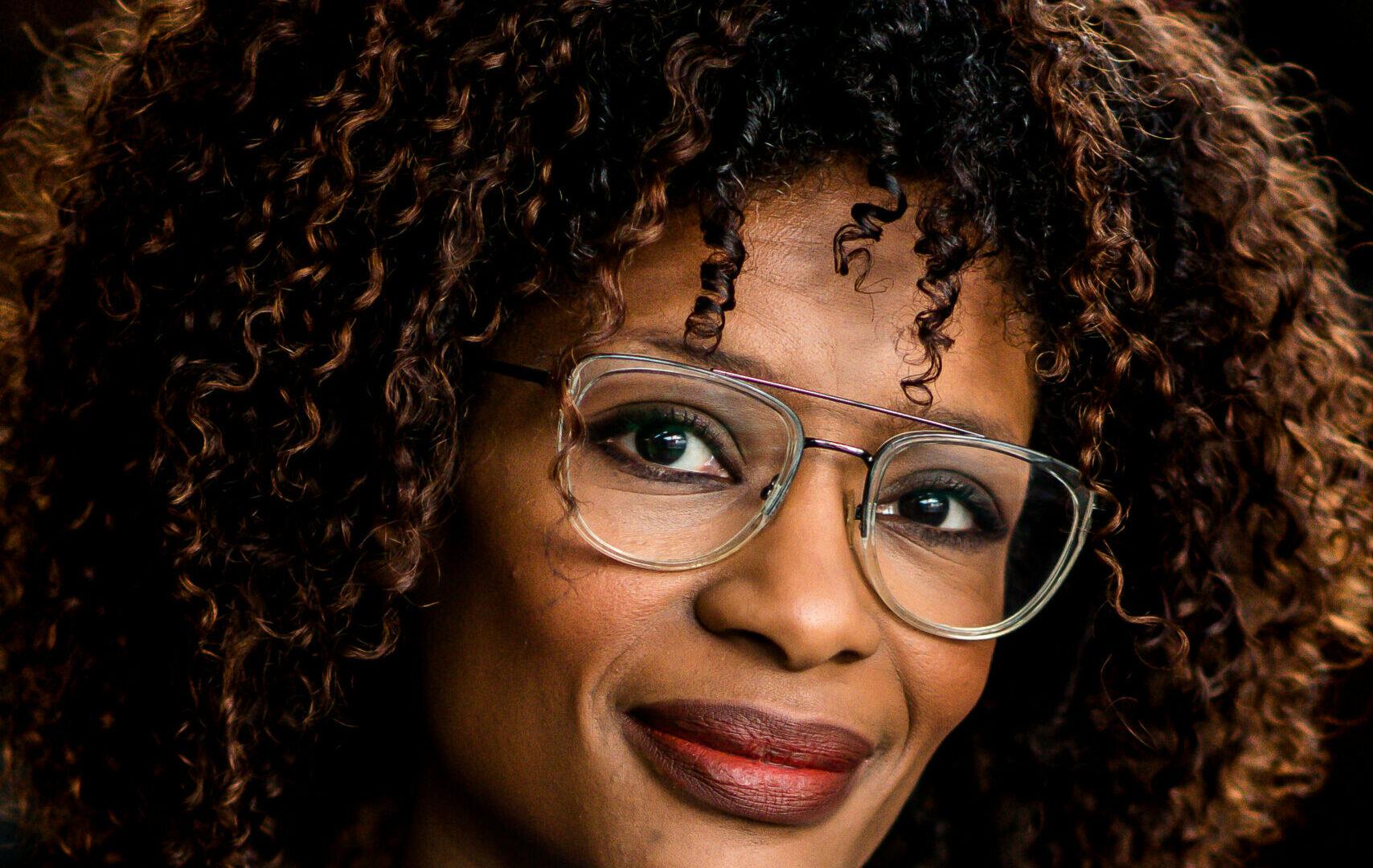 Portretfoto van Sylvana Simons. Ze kijkt glimlachend de camera in. Ze is een zwarte vrouw met halflangvolumineus krullend haar. Ze draagt een bril met doorzichtig pilotenmontuur en een blauwe trui.
