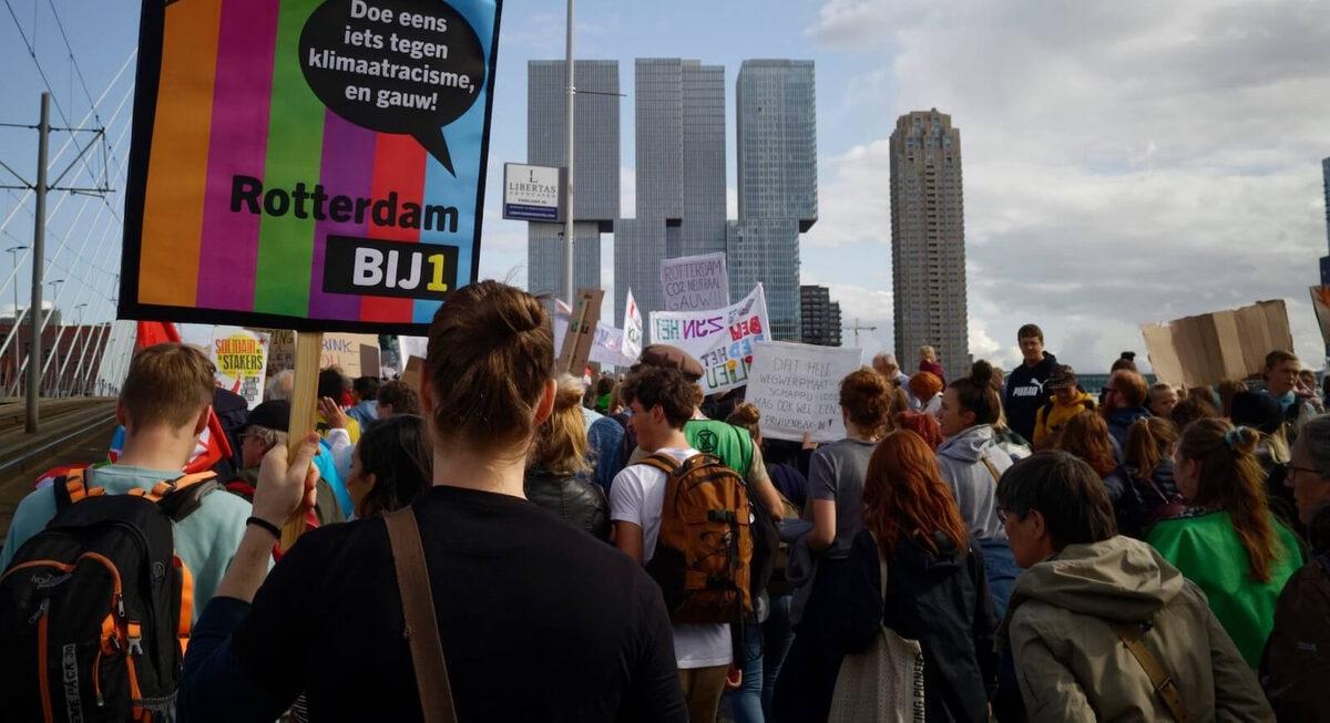 BIJ1 Rotterdam is aanwezig bij de klimaatmars. Ze houden een banner vast met de kleuren van BIJ1.