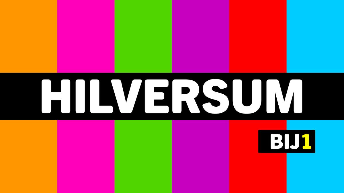 Het logo van Hilversum BIJ1. Oranje, roze, groen, paars, rood blauw, met een zwarte banner waar in witte letters Hilversum staat. Eronder een klein zwart blokje met BIJ1. BIJ is wit, 1 is geel