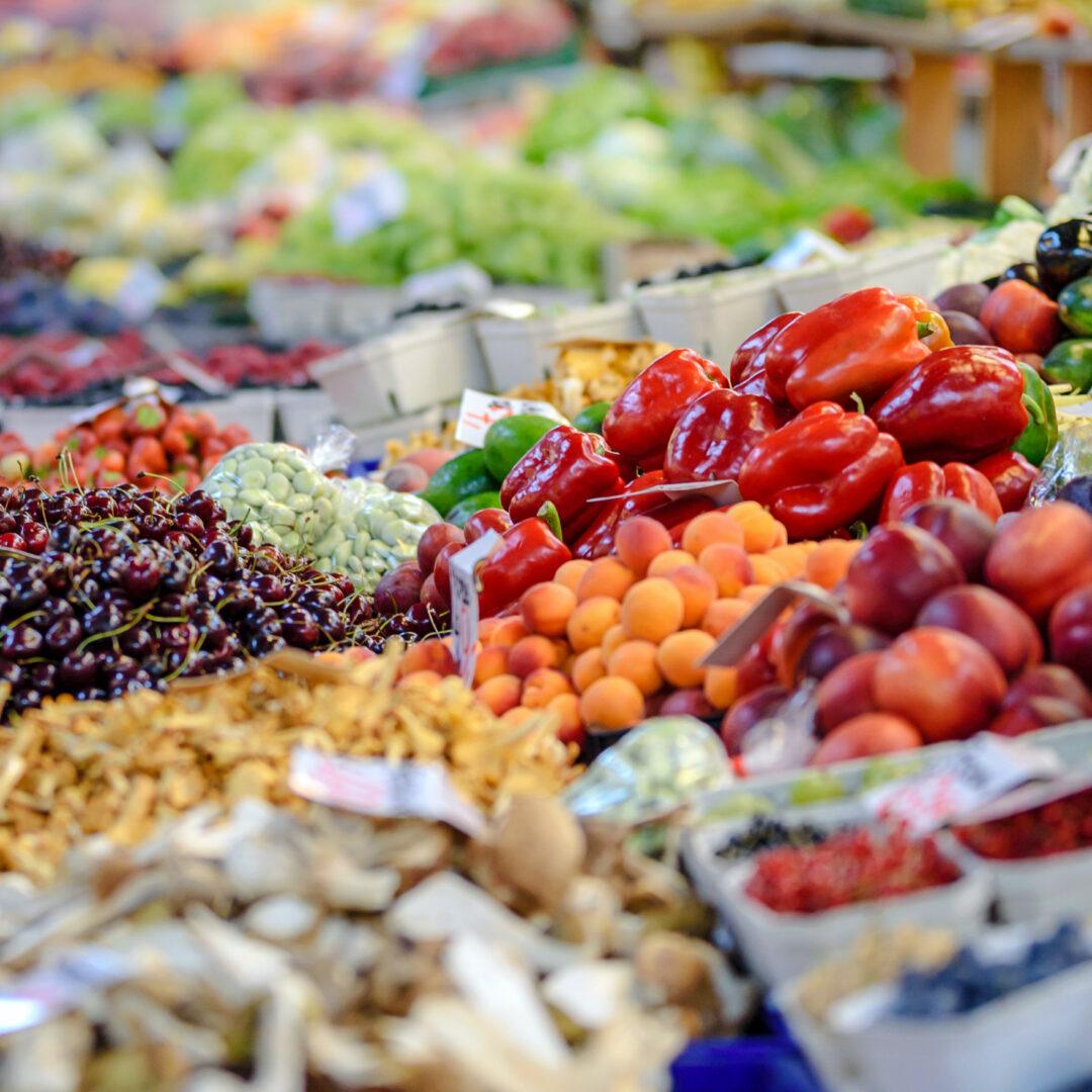 Op een uitgestalde marktkraam liggen allerlei soorten fruit en groenten: druiven, paprika, perzikken, aardappelen.