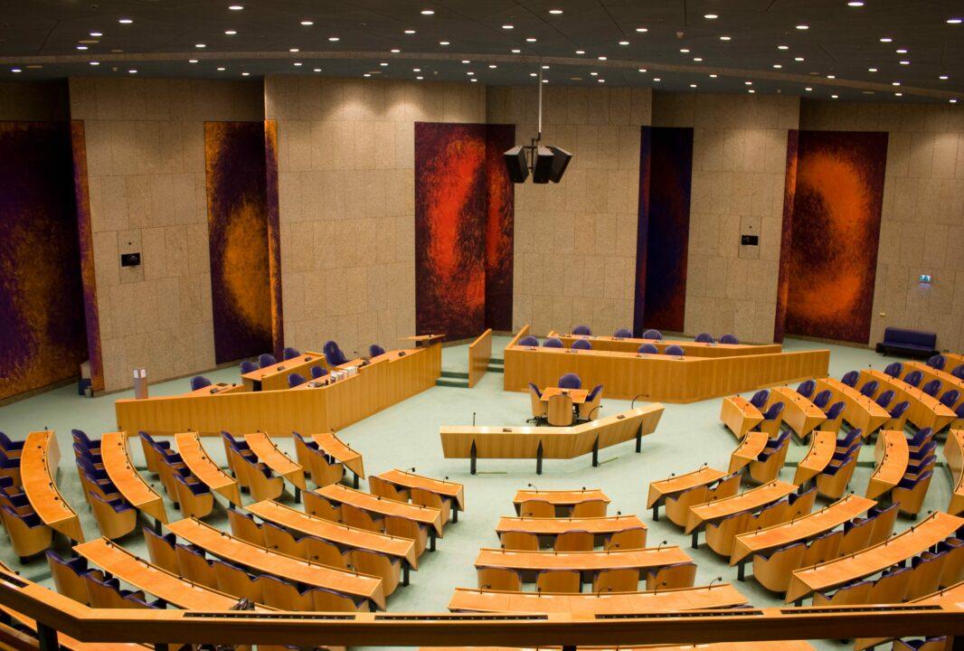 Dit is de pleniare zaal. De stoelen hebben de vorm van een tulp, het tapijt is groen als gras en het plafond heeft de blauwgrijze kleur van de Nederlandse lucht. De zaal moest ook iets van een theater hebben. Vandaar dat de stoelen zijn opgesteld in de halfronde vorm van een Romeins-Grieks theater. De roodpaarse wandpanelen met zeventien lagen olieverf onderstrepen het theatrale karakter.