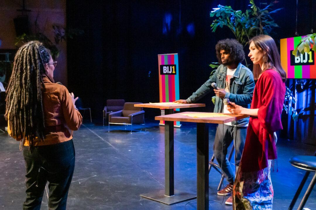 Rebekka en Daryll Ricardo staan achter statafels en hebben microfoons in hun handen. Ze kijken Aldith Hunkar aan, die we van de achterkant zien. Op de achtergrond grote BIJ1 logo's op een banner en een scherm. Presentatrice Aldith Hunkar is een zwarte vrouw met lange locks, Daryll is een zwarte man met afrokapsel en Rebekka is een slanke witte vrouw met lang bruin haar.
