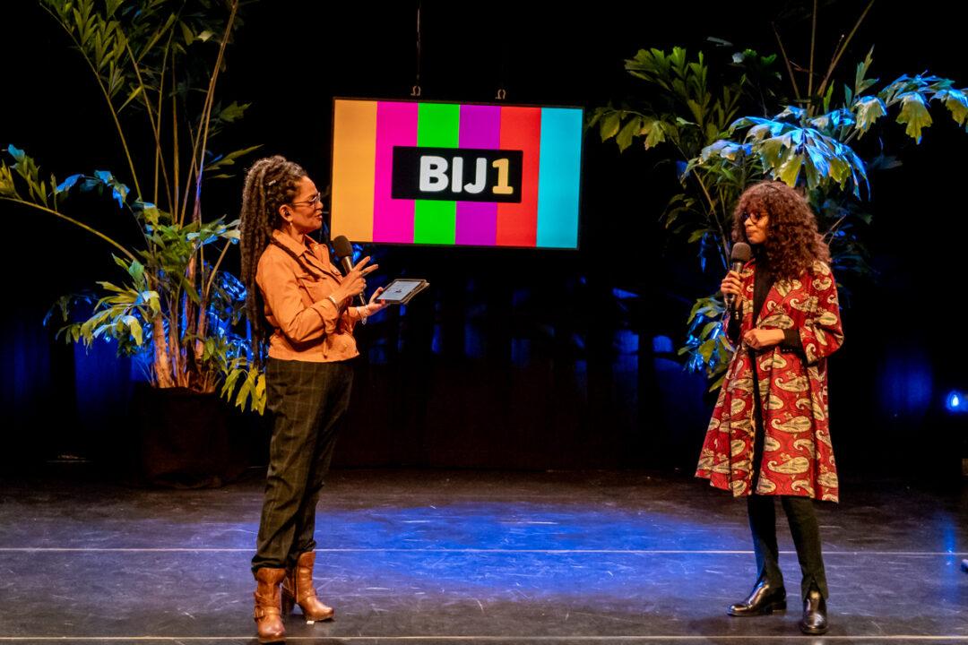 Presentatrice Aldith Hunkar en Sylvana (twee zwarte vrouwen) staan op afstand tegenover elkaar op een podium, ze spreken in microfoons. Achter hen staan grote planten en een scherm met het BIJ1 logo erop