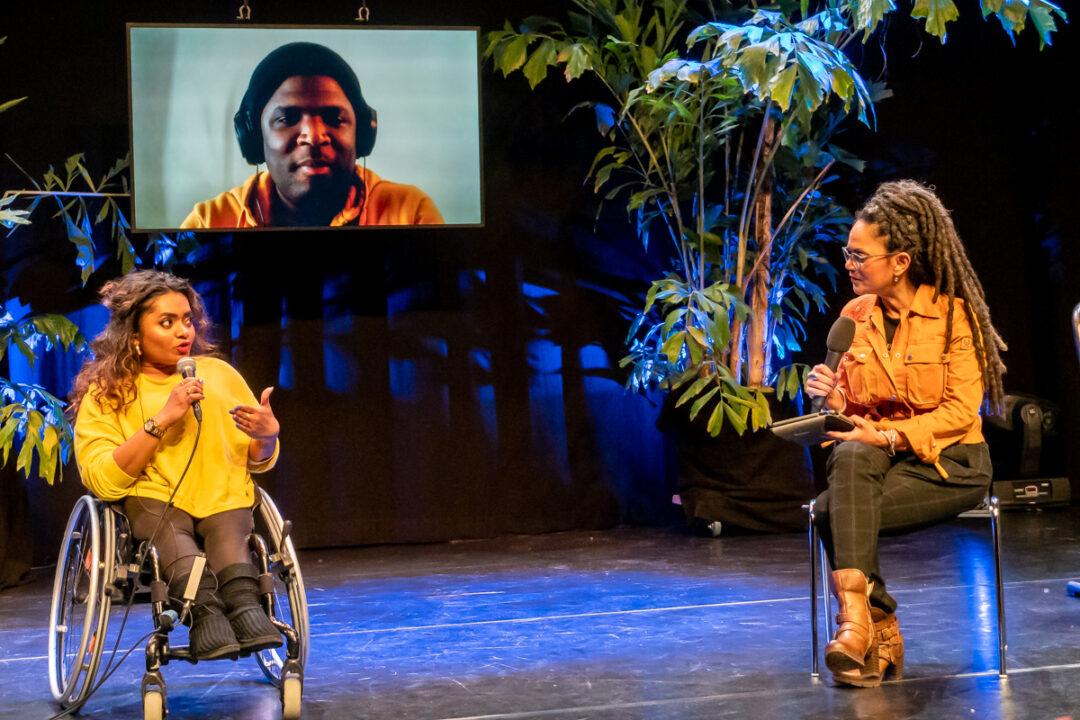 Jeanette Chedda zit in haar rolstoel en praat in een microfoon, presentatrice Aldith Hunkar zit op een afstandje naast haar en spreekt met haar, ook in microfoon. Op de achtergrond is Quinsy Gario zichtbaar op een groot scherm.