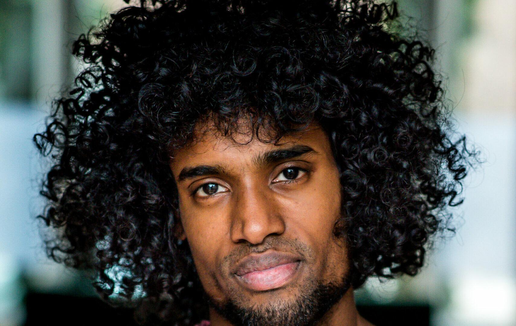 Portret van Daryll Ricardo Landbrug. Hij is een zwarte man met een sikje en een groot afro-kapsel. Hij draagt een roze trui en kijkt vriendelijk en serieus de camera in.