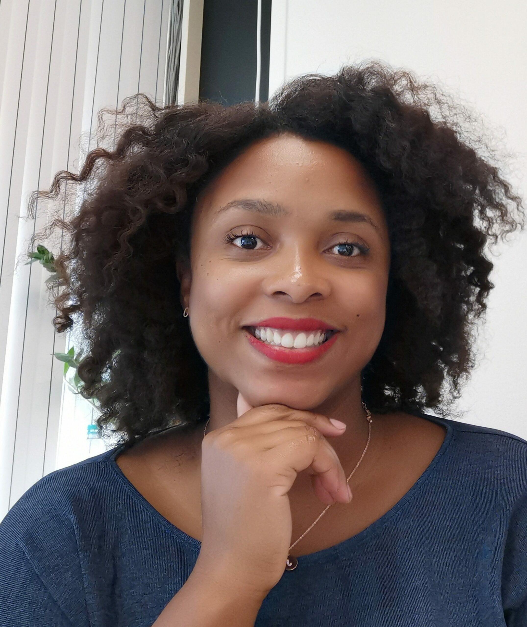 Zwarte vrouw met rode lippenstift, zwarte krullen en een blauwe blouse