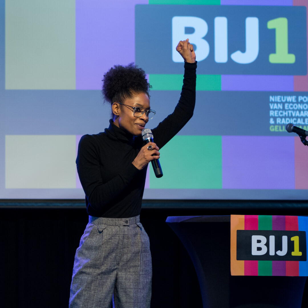 Sylvana staat voor een digitaal scherm met BIJ1 logo, ze heeft een microfoon in haar rechterhand en haar linkervuist steekt ze in de lucht. Ze is een slanke zwarte vrouw met haar krullende haar opgestoken op haar hoofd. Ze draagt een zwarte koltrui en een grijs geruite broek.