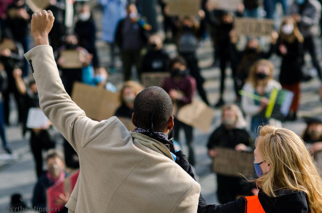 We zien de achterkant van een persoon die bij een protest zijn vuist omhoog steekt. Hij staat op een verhoging. Er staan protestanten naar hem te kijken die kartonnen bordjes met Black Lives Matter leuzen omhoog houden.