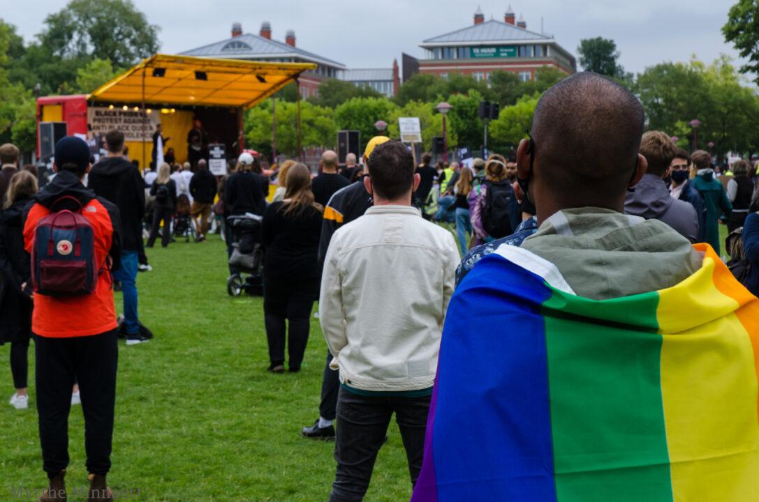 Een zwarte man heeft een regenboogvlag om zijn schouders. Hij staat tijdens ene protest op een grasveld naar het podium te kijken. Voor hem staan meer demonstranten op anderhalve meter afstand van elkaar
