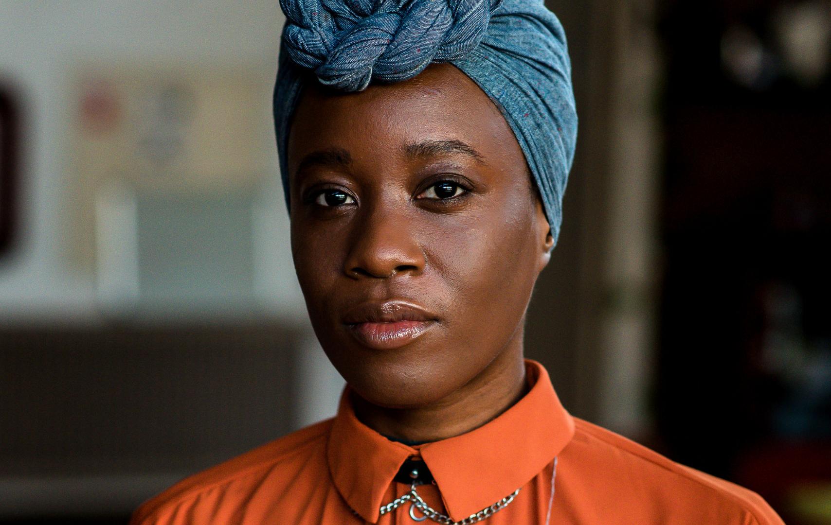 Portretfoto van Michantely de Jong. Een zwarte vrouw met een blauwe hoofddoek op. Ze draagt een oranje blouse.