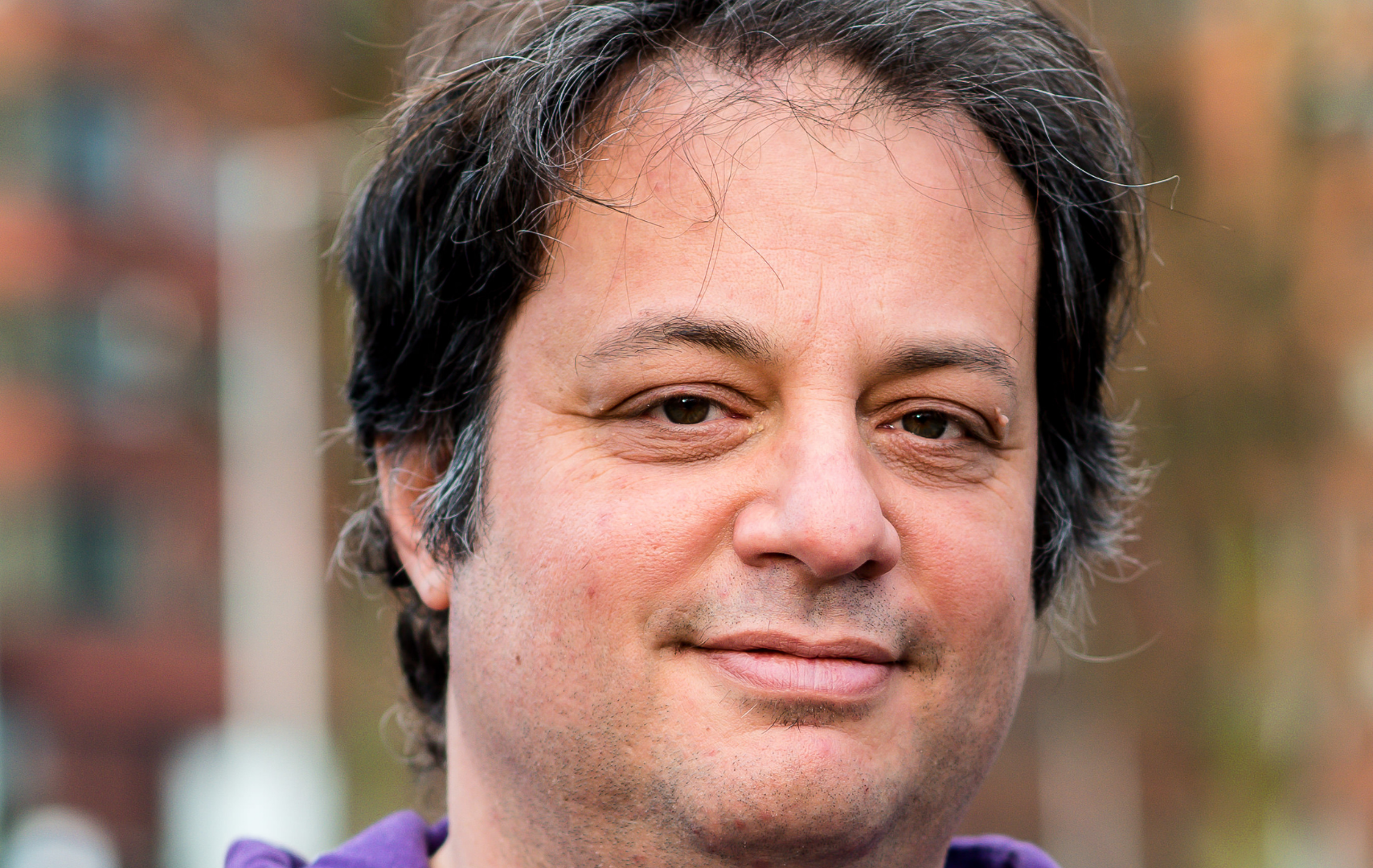 Portretfoto van Yuval. Hij heeft zwart haar en draagt een paars vest.