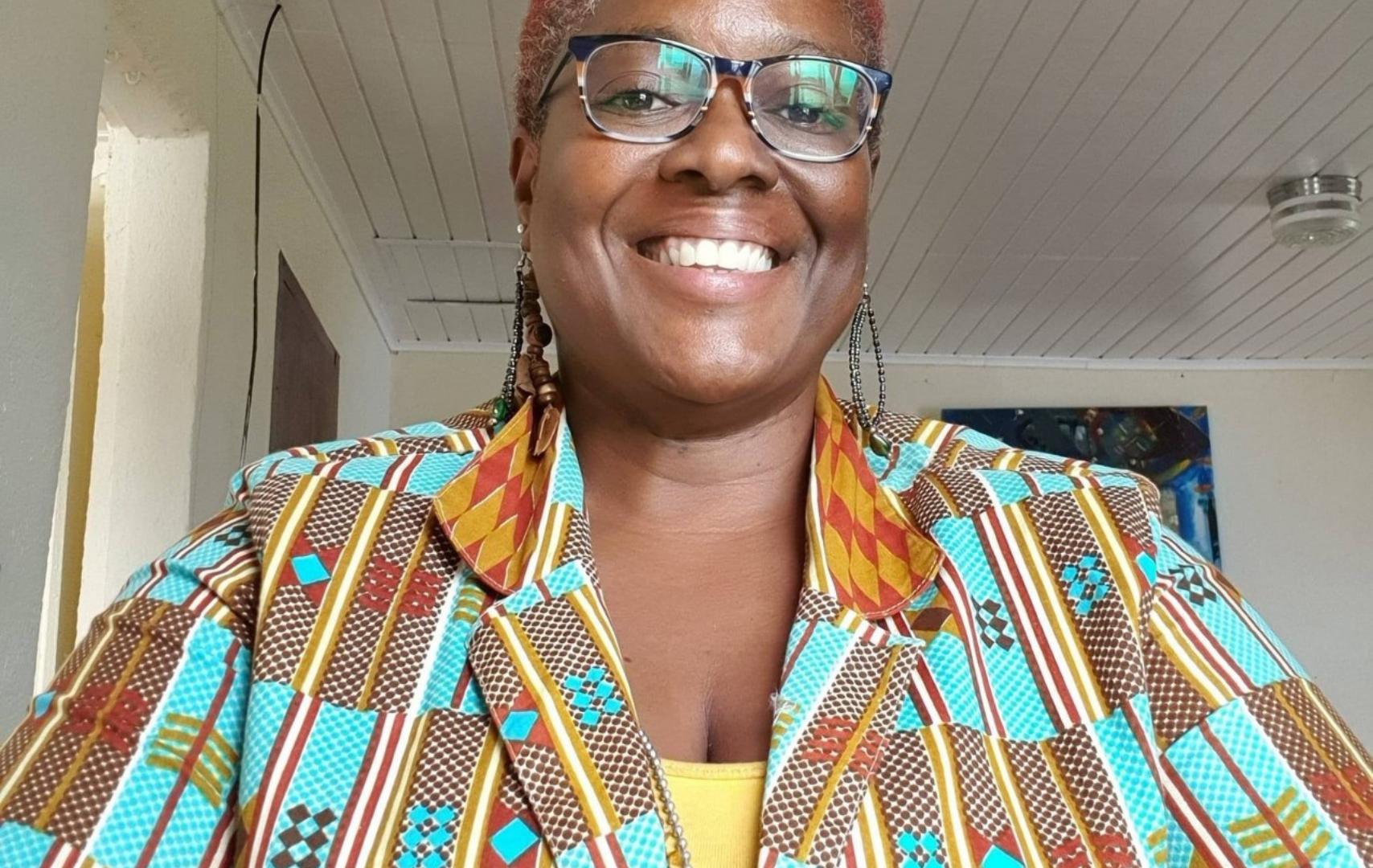 Foto van Lysanne Charles. Zij is een zwarte vrouw met roodgeverfd haar. Ze draagt een donkere bril en een kleurrijke blouse.