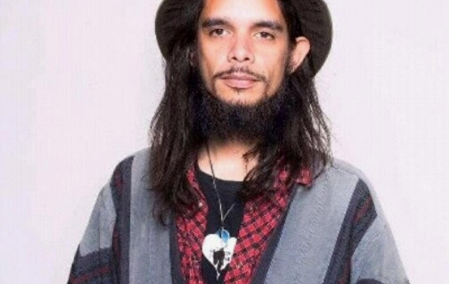 Foto van Miko-Serko. Hij heeft lang donker haar en een baard. Hij draagt een hoed en een rood-zwart shirt. Daaroverheen een grijs jack.