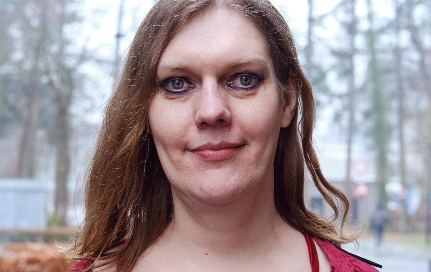 Portretfoto van Petra Kramer. Zij is een witte vrouw en draagt een rode