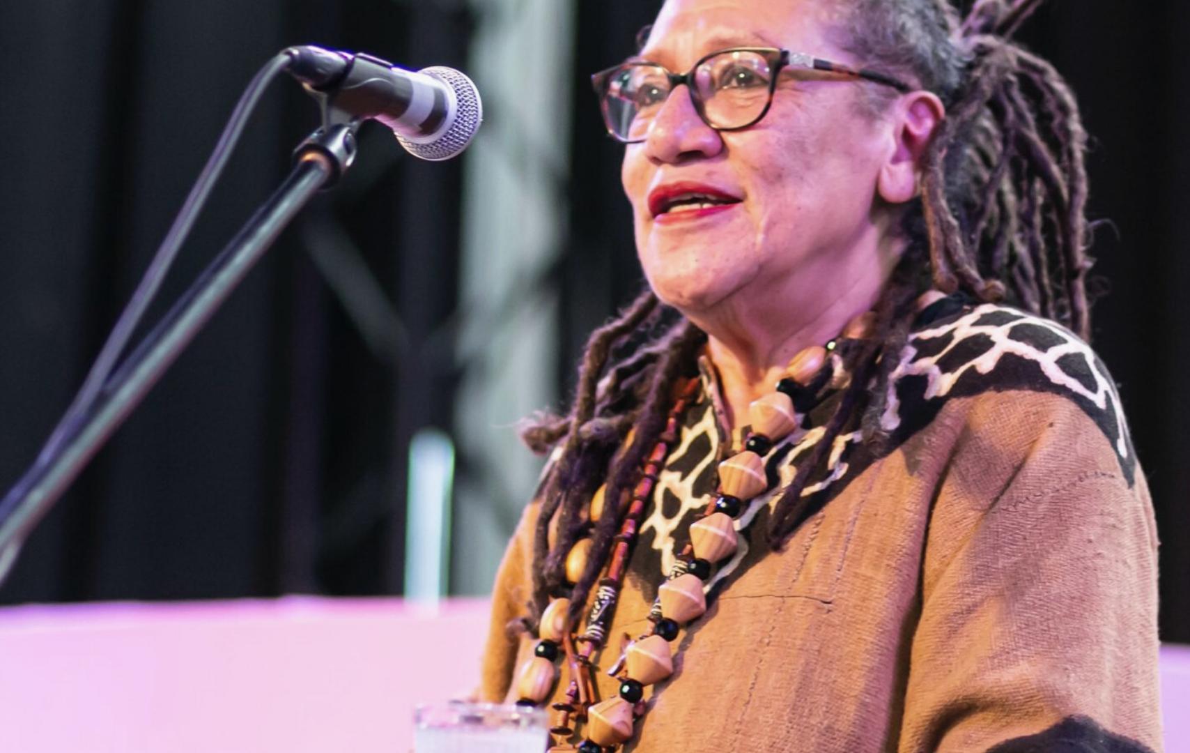 Foto van Gloria Wekker. Zij staat op een podium, achter een microfoon. Ze heeft een donkere bril en lang, grijs-zwart haar.