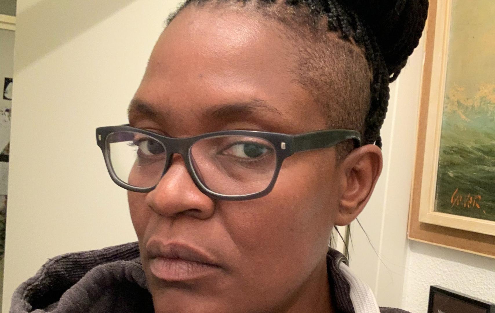 Foto van Romana Vrede. Zij is een zwarte vrouw en draagt een zwarte bril.