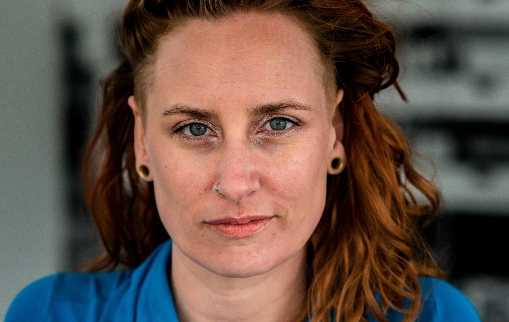 Portretfoto van Yvette. Hen heeft rood haar met en slag en en draagt een blauwe jurk.