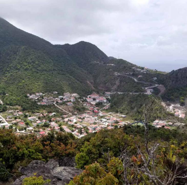 Een berglandschap, vanaf de hoogte gefotografeer. We zien tussen de heuvels een cluster aan huizen liggen. Dit is het eiland Saba