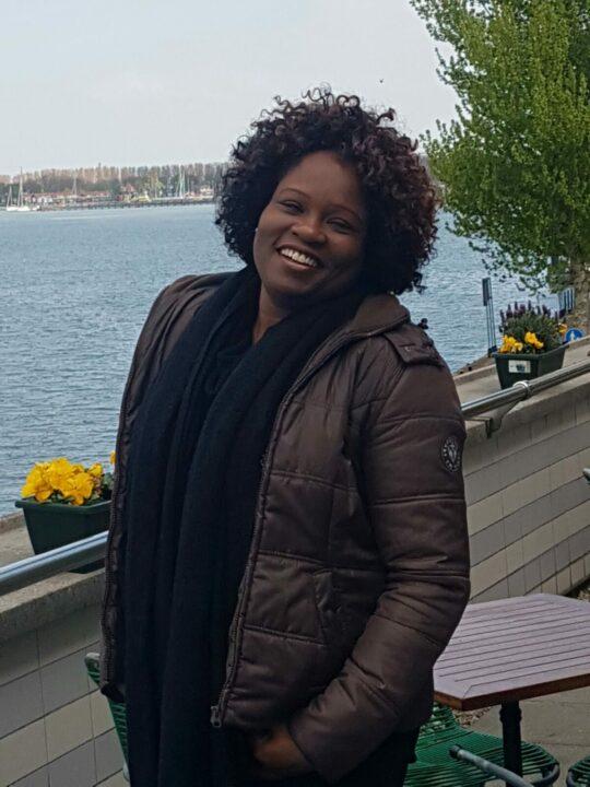 Foto van Cheryl Vliet, zwarte vrouw breed lachend met krullend haar.