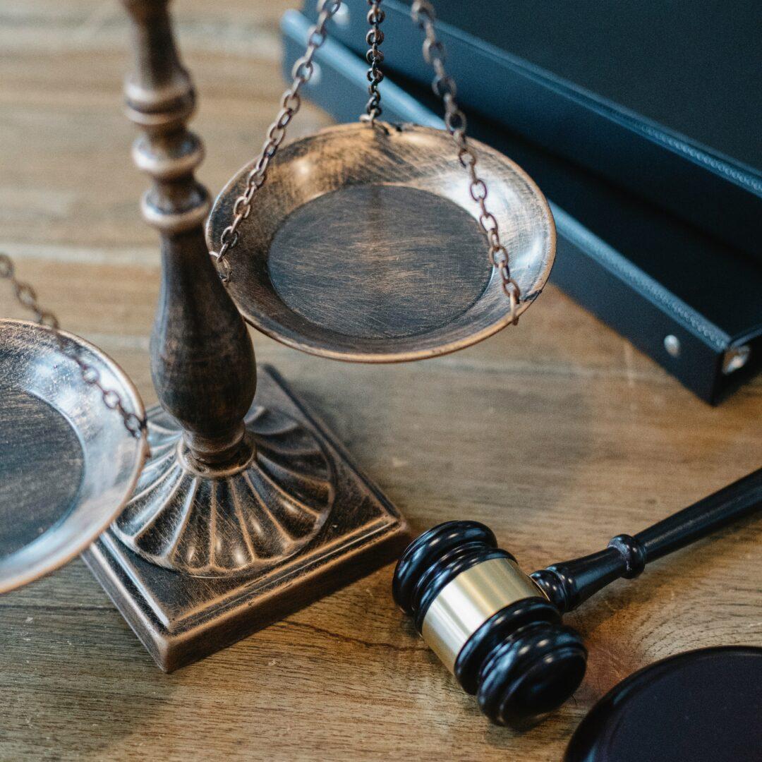 We zien een koperen weegschaal met een houten hamer, als symbool voor het recht en gerechtigheid