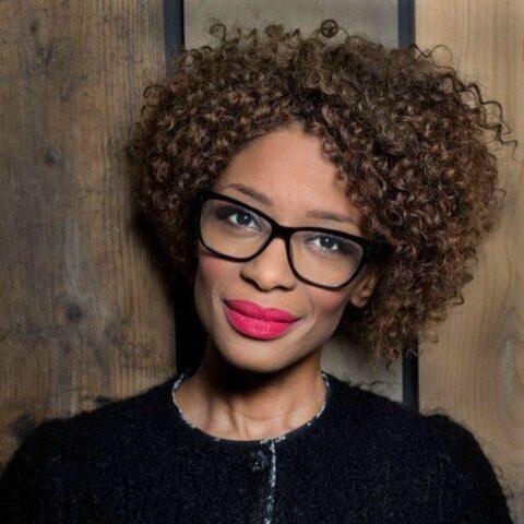 Portretfoto van Sylvana Simons. Haar bruine haar krult in een korte bob, ze draagt en bril en frambooskleurige lippenstift. Ze kijkt met een glimlach de camera in.