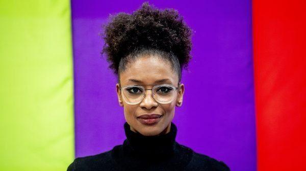Portretfoto Sylvana Simons. Haar haar zit strak in een paardenstaart, ze heeft een randloze bril en een zwarte coltrui aan. Achter haar zien we de groene, paarse en rode kleur van de BIJ1 kleurenbalk
