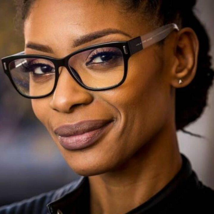 Portetfoto van Sylvana Simons, ze kijkt schuin de camera in met een glimlach. Ze draagt een zwarte bril en draagt licht roze lippenstift. Ze glimlacht.