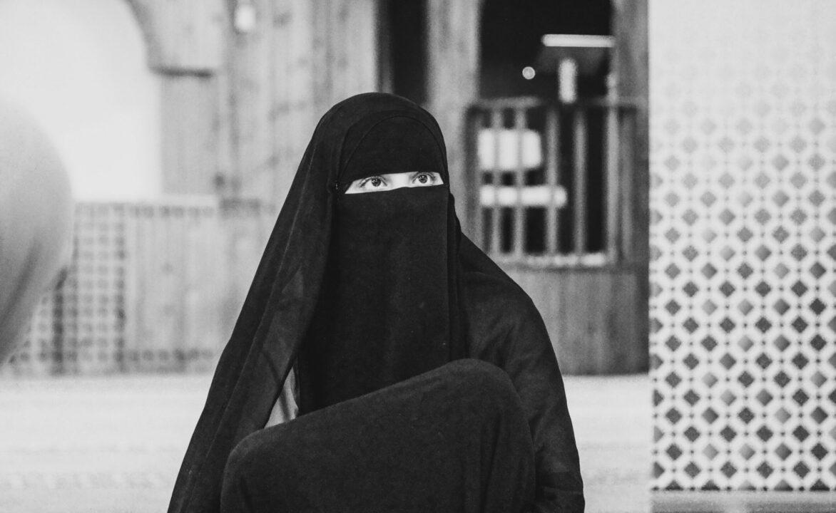 Zwart-wit foto van een vrouw in niqab. Op de achtergrond een hekje en een muur met tegeltjes erop.