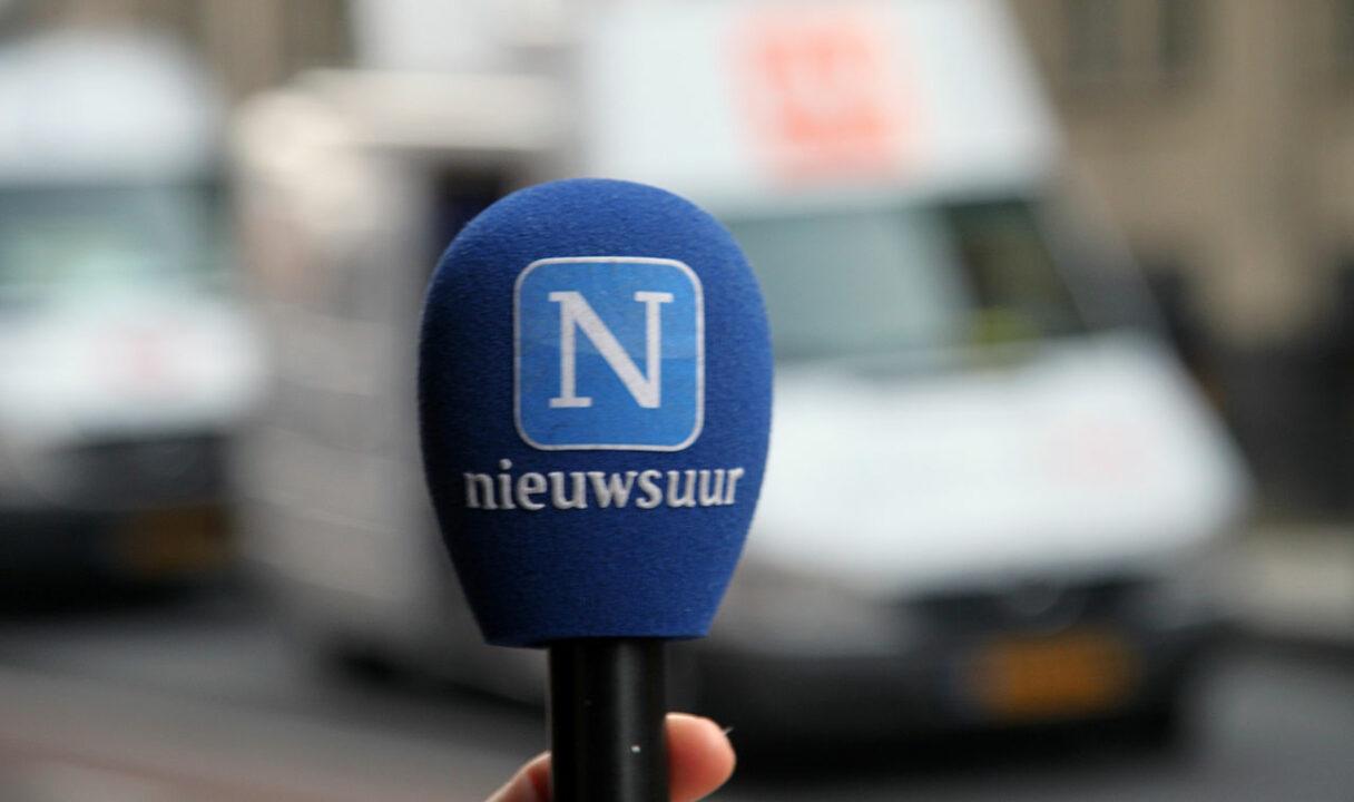 Foto van een microfoon met blauwe plopkap met het Nieuwsuur-logo erop.