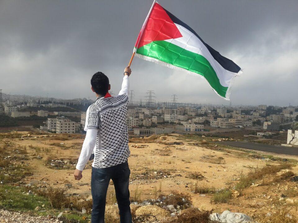 Persoon met een Palestijnse vlag voor een Israelische nederzetting.