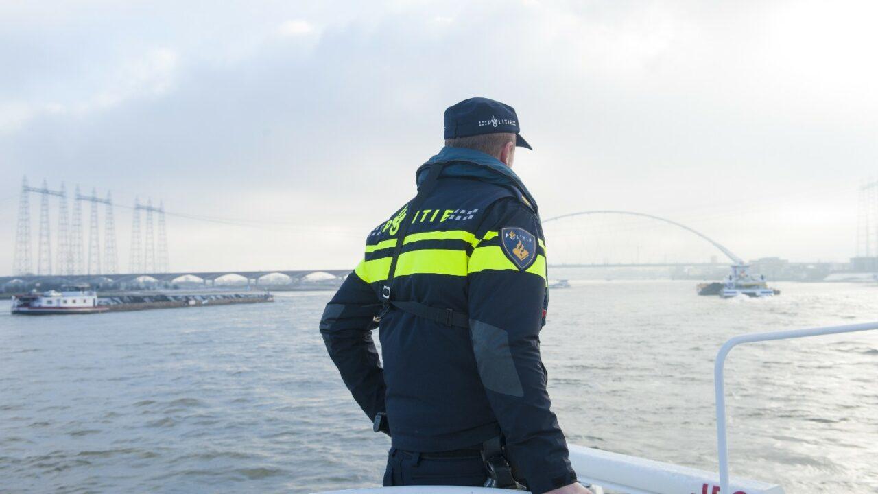 Een politieagent kijkt over het water. We zien zijn rug, hij draagt een donkerblauwe jas met gele strepen waar het logo van de politie op staat.